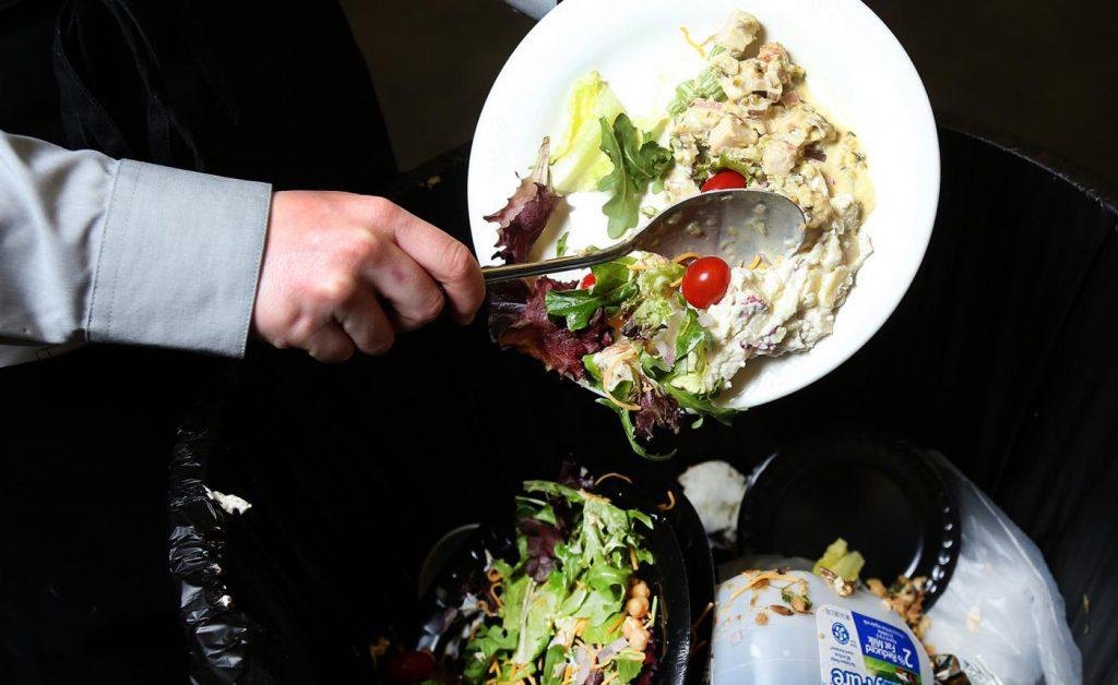 Tirando la comida a la basura en un restaurante.